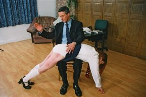 Steve Bickers spanks grown up schoolgirl Therese in a scene from the video The Headmaster's Study