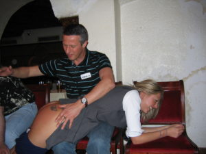 Steve Bickers spanking a girl's bare bottom at a Kane spanking party