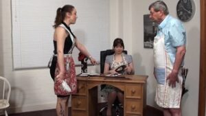 When Miss Akroyd called Donald to her office for discipline it was clear she was looking forward to it. I joined her and we both put on our punishment pinnies. I made him stand up while I took a plimsoll from Miss Akroyd's desk drawer, then a slipper, before offering her the choice of weapon. She took the slipper so I had the heavy plimsoll to blister his bottom. We stood on each side of him and Miss Akroyd was using a vicious backhand swing. He was crying in moments. How he wailed as we slippered him in unison. He blubbered and begged for mercy so we gave him some rapid hard strokes and sent him to the corner. My phone rang and I put Donald on videocall to humiliate him, then took a riding whip to his bare bottom. We'd give him 6 strokes each. Before long his bottom was getting very striped. It was clearly hurting him but I showed no mercy. He snivelled and blubbered so I gave the whip to Miss Akroyd and asked her to carry on. She was disappointed she could only give him 6 but she lashed his backside, raising some livid weals across his bottom that show up well in the close-up. Then we set him 650 lines to do and ordered him out of the room.